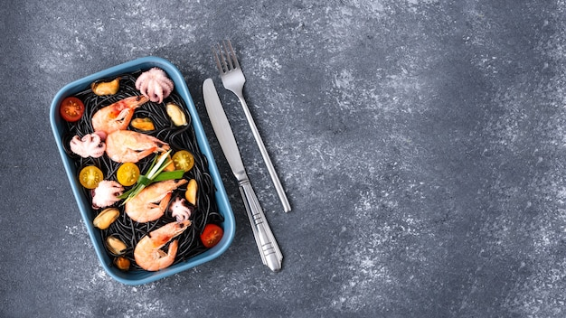 Top view of black pasta with seafood-king prawns, mussels, octopuses, cherry tomatoes in blue plate with fork and knife on gray background with copy space