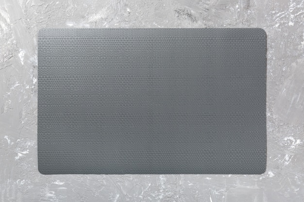 Top view of black place mat for a dish. cement background