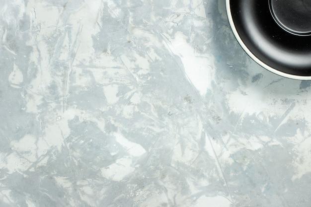 Vista dall'alto piatto nero rotondo vuoto formato su sfondo bianco piatto di vetro colore alimentare