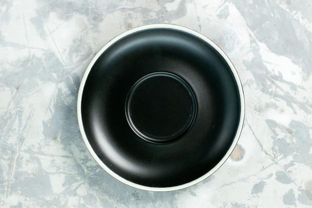 Vista dall'alto piatto nero rotondo vuoto formato su un colore alimentare di vetro piatto superficie bianca