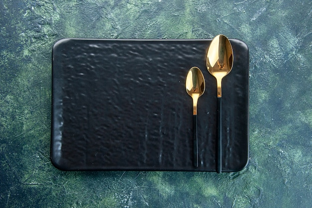 Top view black plate with golden spoons on dark blue background food utensil color dinner restaurant service meal cutlery