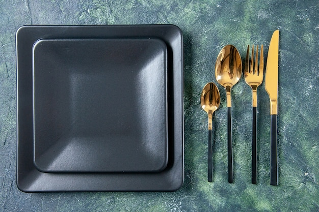 Top view black plates with golden fork spoons and knife on dark background color food cutlery restaurant service dinner kitchen cafe