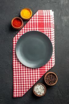 Vista dall'alto piatto rotondo nero su ciotole di tovaglioli a scacchi rossi e bianchi con curcuma pepe rosso in polvere sale marino pepe nero sul tavolo scuro