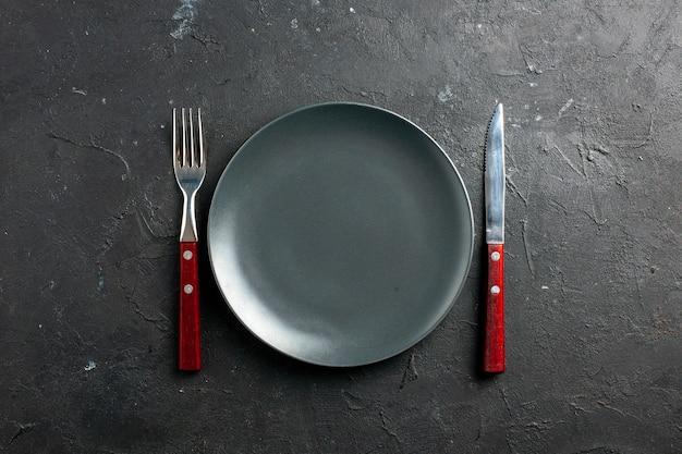 검은 표면에 상위 뷰 블랙 샐러드 접시 포크와 나이프