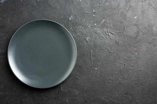 Вид сверху черная салатная тарелка на черной поверхности с местом для копирования