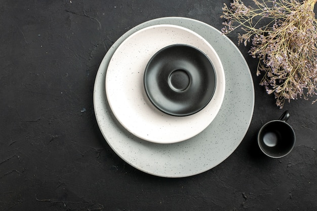 Top view black saucer and white plate on grey plate black cup dried flower branch on dark surface free space