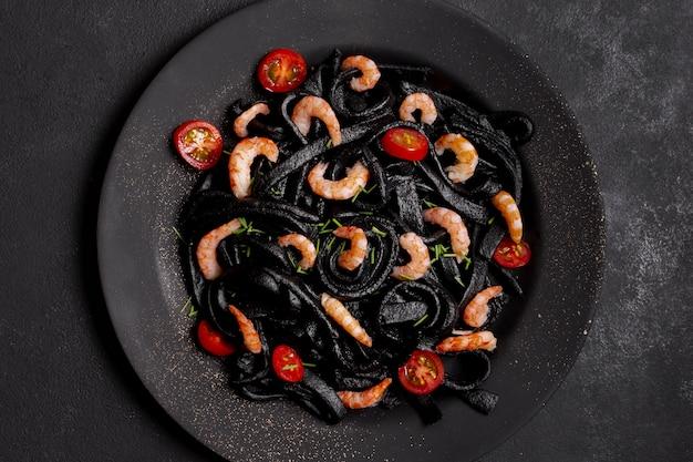 Вид сверху черная паста с креветками на тарелке