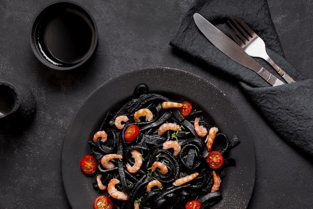 Top view black shrimp pasta with soy sauce and cutlery