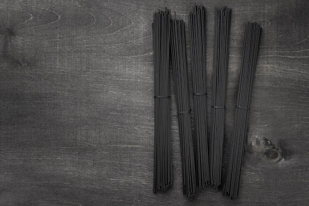 Top view of black spaghetti bundles with copy space
