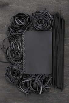 Top view of black spaghetti and tagliatelle with notebook
