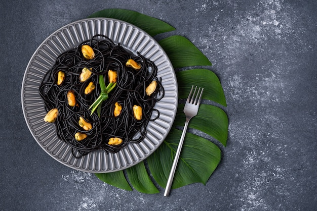 Top view black spaghetti with ink cuttlefish with mussels in grey plate with fork on green leaf on grey background with copy space
