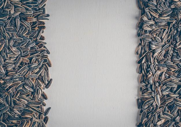 흰색 배경에 상위 뷰 검은 해바라기 씨앗. 텍스트를위한 수평 여유 공간