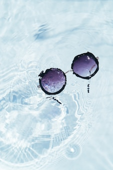 Top view of black sunglasses on pool water surface