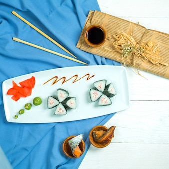 Top view of black sushi rolls with salmon served with ginger and soy sauce on blue and white