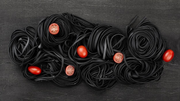 Top view of black tagliatelle with tomatoes