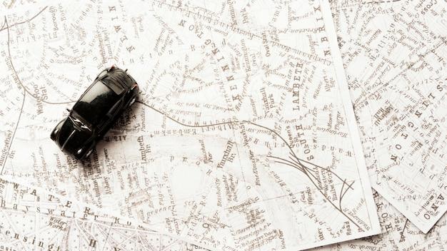 Вид сверху черный игрушечный автомобиль на картах