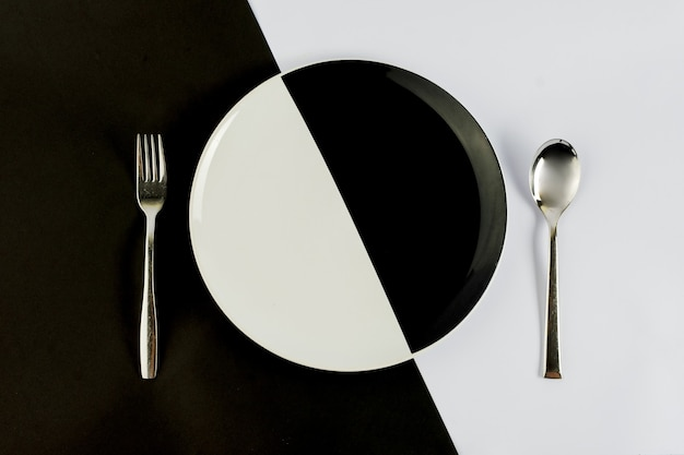 Top view of black and white colors of plate with silver spoon and fork on a black and white table