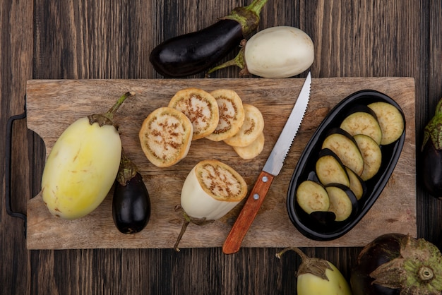 Top view black and white eggplant slices on cutting board with knife on wooden background
