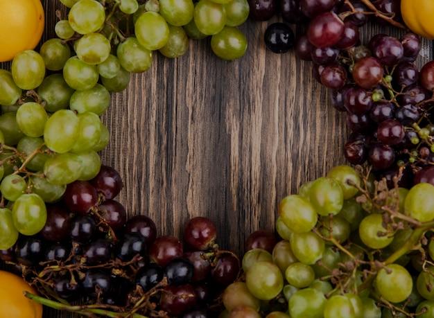 Vista dall'alto di uva in bianco e nero con albicocche su fondo di legno con lo spazio della copia