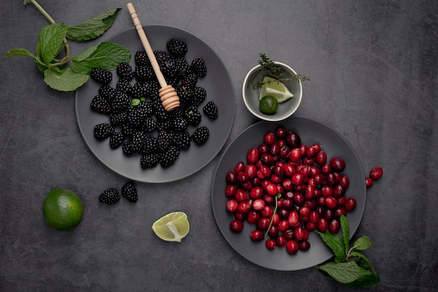 Top view of blackberries and cranberries on plate with mint and honey dipper