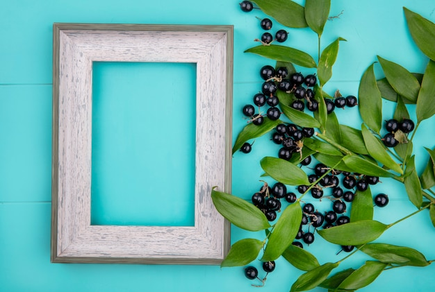 Top view of blackberry in a bowl with leaf branches on a light blue surface