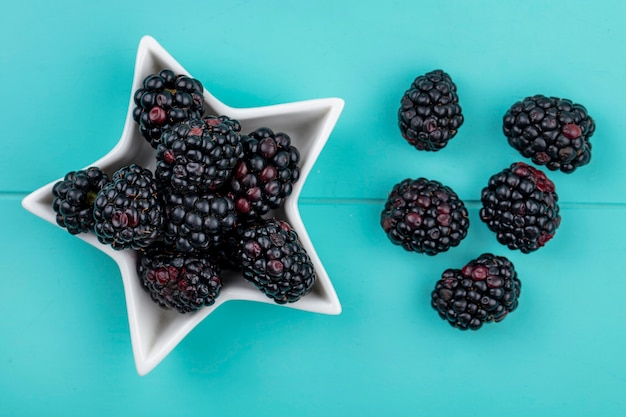 Top view of blackberry in a saucer in the form of a star on a light blue surface