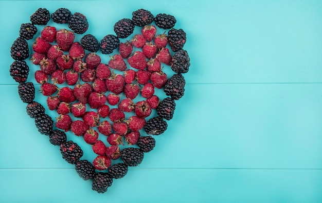 Top view of blackberry with raspberries heart-shaped on a light blue surface