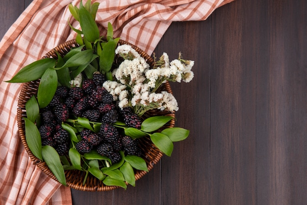 Top view of blackberry with white flowers in a basket with a checkered cinnamon towel on a wooden surface