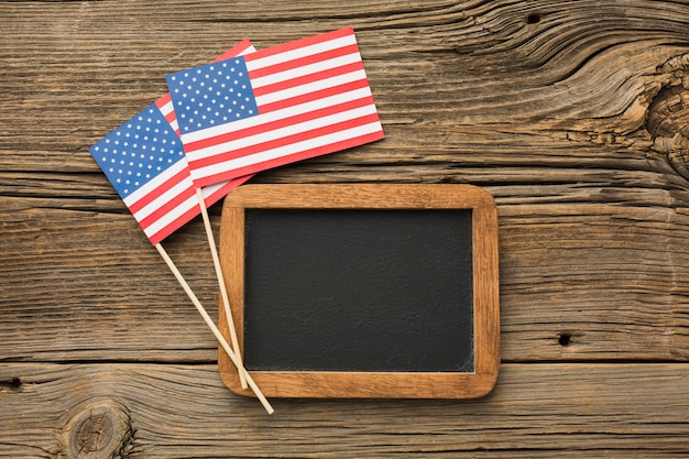 Top view of blackboard and american flags on wood