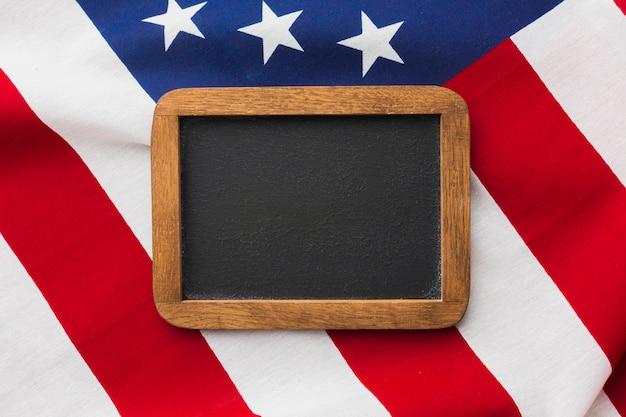 Top view of blackboard on top of american flag