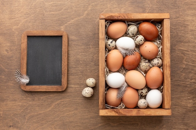 Top view of blackboard with box full off eggs for easter