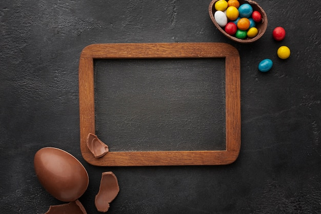 Top view of blackboard with chocolate easter eggs filled with colorful candy