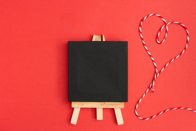 Top view of a blackboard with heart thread on a red background