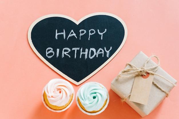 プレゼントとカップケーキのあるトップビュー黒板