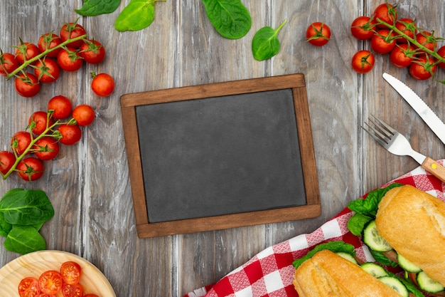 Top view of blackboard with tomatoes and sandwiches