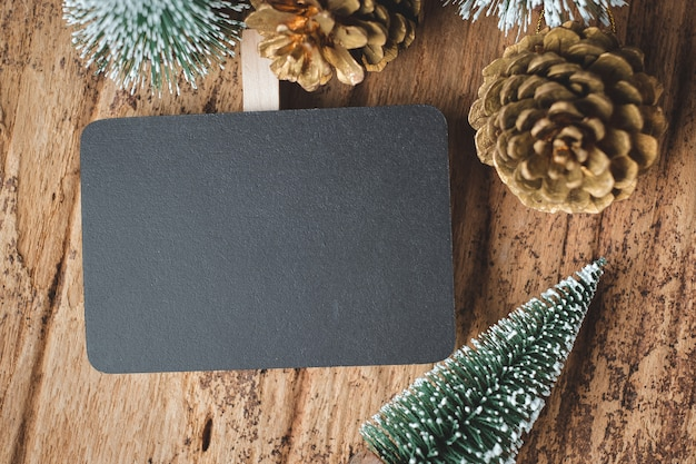Top view of blank blackboard with xmas tree and gold pine cone