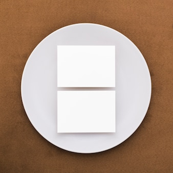 Вид сверху пустых визиток на тарелке