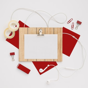 Top view of blank clipboard over red supplies