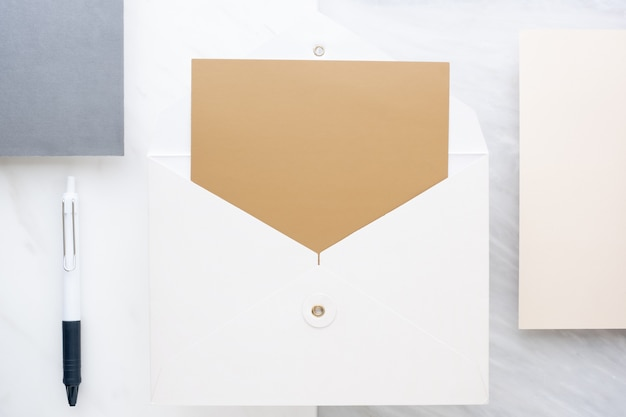 Top view of  blank golden card in white envelop on table