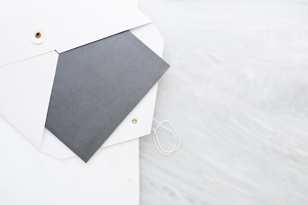 Top view of blank grey card in white envelop on two layer step of marble table