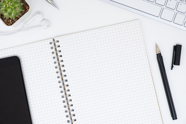 Top view of blank grid notebook page on top of white office table, flat lay.