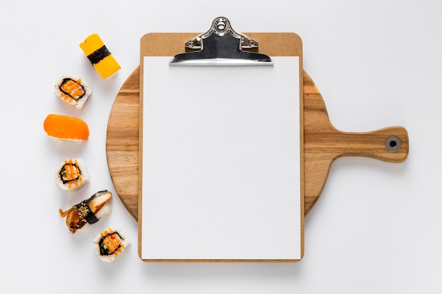 Top view of blank menu on chopping board with sushi