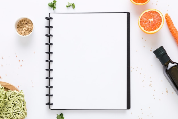 Top view of blank menu notebook with olive oil and carrot