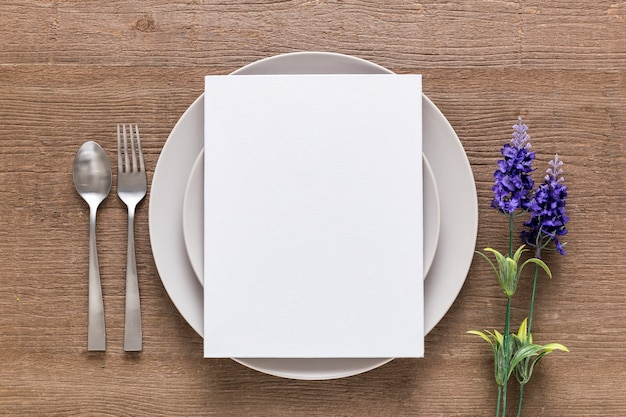Top view of blank menu paper on plate with flowers and cutlery