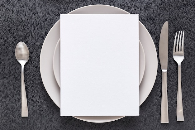 Top view of blank menu paper on plate with fork and knife