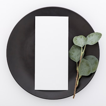 Top view of blank menu paper on plate with plant