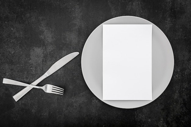 Top view of blank menu paper with plate and cutlery