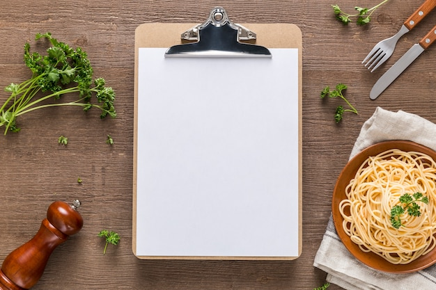 Top view of blank menu with pasta and cutlery