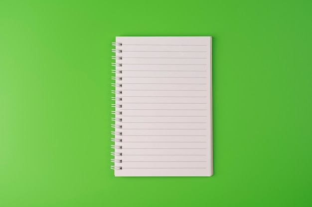 Top view of blank note paper on green background back to school and education concept copyspace
