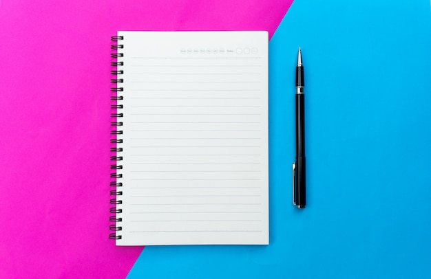 Top view blank notebook and black pen for mockup flat lay on blue and pink background.